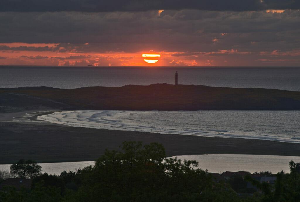 le soleil se couche derrière la phare de a Frouxeira